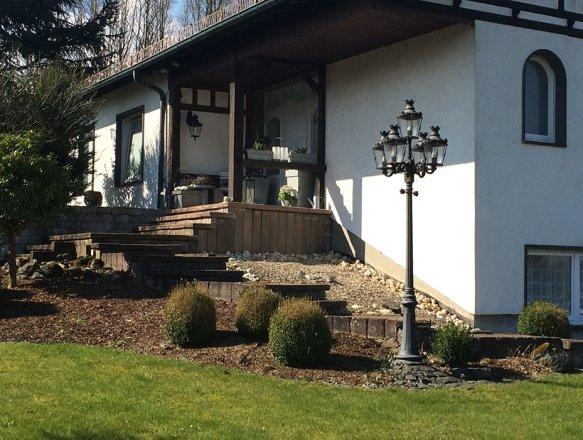 Die 5flammige Baden-Baden Boulevardlaterne (Nr.2485 BB1) beleuchtet hier den Treppenaufgang zum Haus, eine hängenden Wandleuchte (Nr.2439 BB1) sorgt im Eingangsbereich neben der Haustür für gutes Licht.